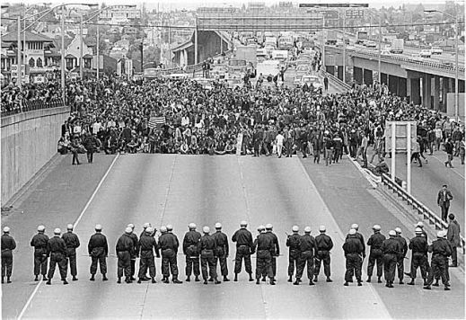 May 5, 1970: Thousands of University of Washington students occupying and blocking Intersate Highway 5 (I-5) and facing state troopers in riot gear as they protested the killings at Kent State Universtiy and the invasion of Cambodia. Photo, Museum of History & Industry, Seattle.